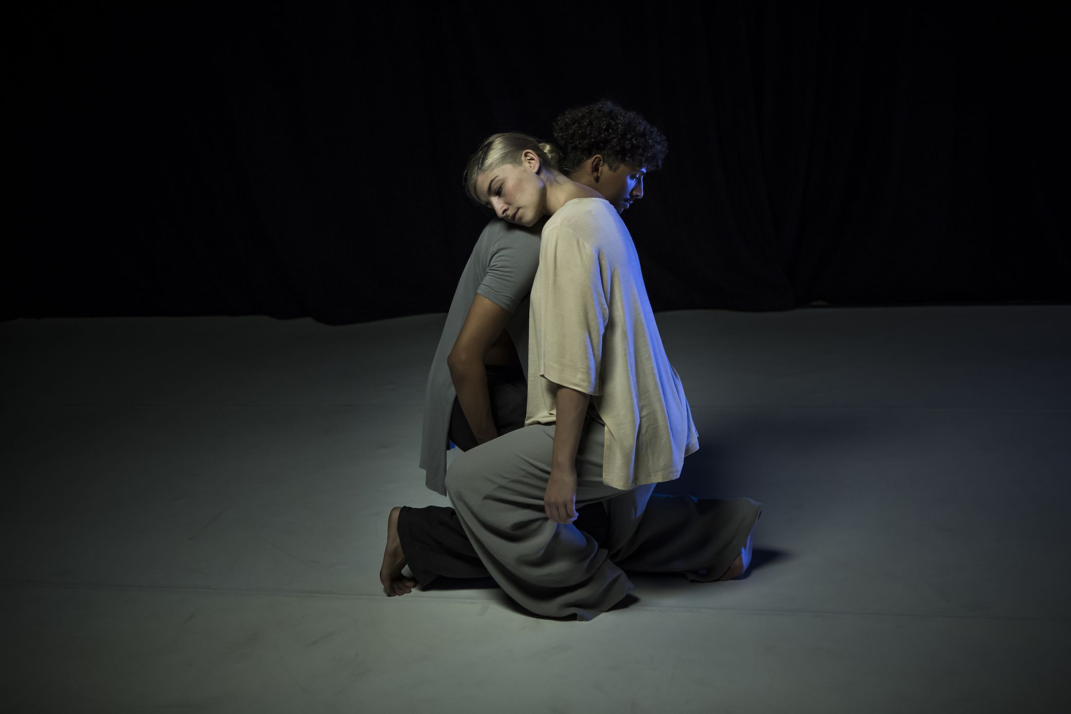 Two dancers leaning against eachother